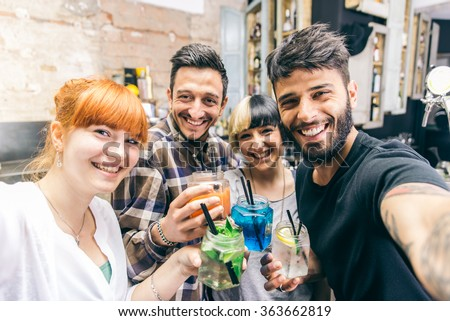 Friends having fun in a bar with cocktails, and taking selfies - stock photo