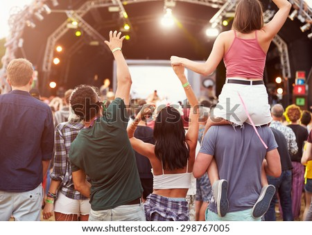 Friends having fun in the crowd at music festival, back view - stock photo