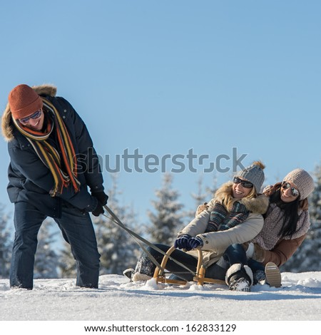 Friends having fun on snow sledge sunny wintertime - stock photo