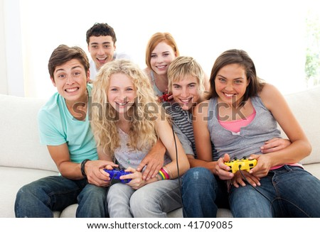 Friends having fun playing video games in the living-room