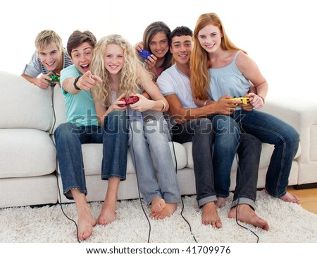 Friends having fun playing video games in the living-room - stock photo