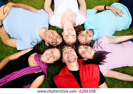 friends having fun portrait in a park lying on the grass with heads together - stock photo