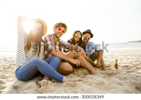 Friends having fun together at the beach and drinking a cold beer - stock photo