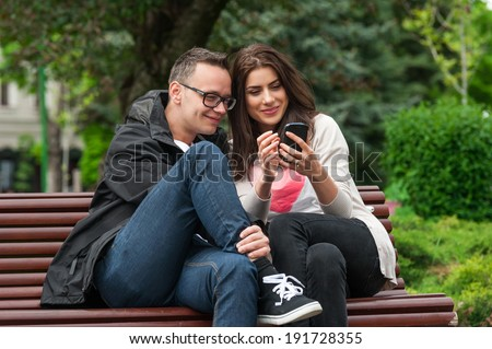 Friends having fun watching something on mobile phone,laughing smiling happy on a bench in park. Outdoor. - stock photo