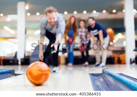 Friends having fun while bowling and spending time together - stock photo
