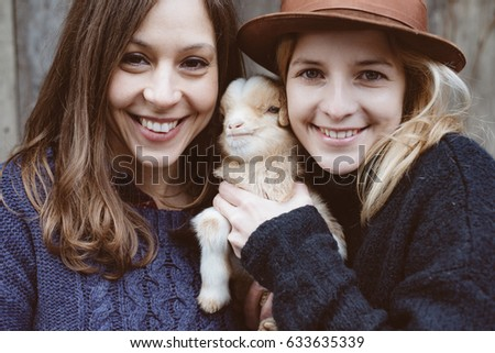 Friends having fun with farm animal at farm