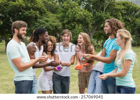 Friends having fun with powder paint on a sunny day - stock photo