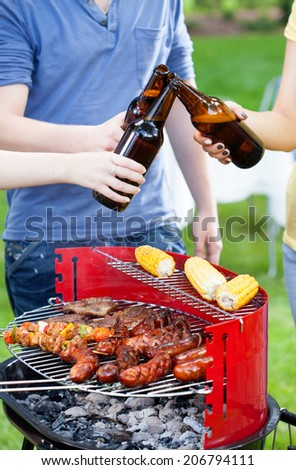 Friends having good time during grilling and drinking beer - stock photo