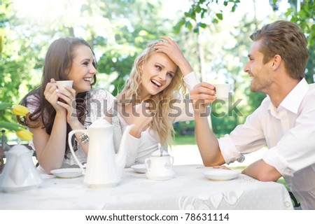 Friends having good time in summer garden - stock photo