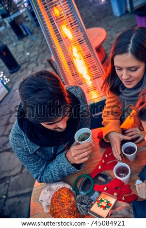 Friends Having Hot Drinks Outdoors On Winter Market