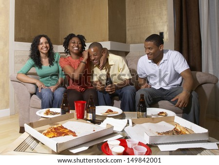 Friends having pizza party at home - stock photo