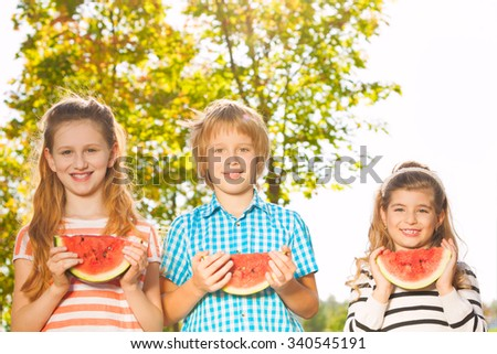 Friends hold watermelon and eating together in row