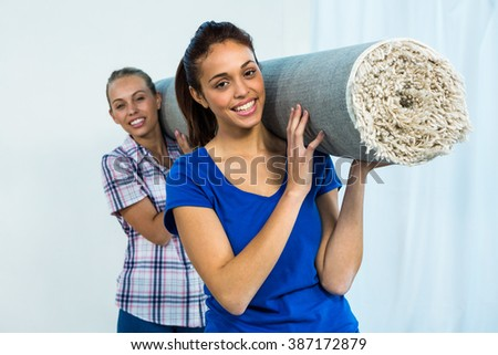Friends holding a carpet to move it - stock photo