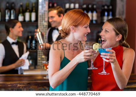 Friends holding a cocktail in front of bar counter in bar