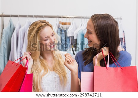 Friends holding a credit card while carrying shopping bags - stock photo
