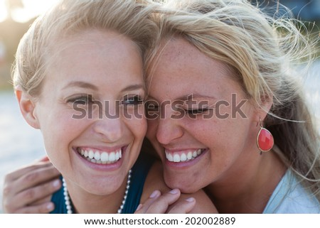 Friends hug and smile while sharing a joyful moment on the beach - stock photo