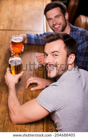 Friends in bar. Top view of two happy young men drinking beer at the bar counter and smiling - stock photo