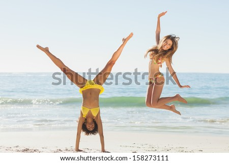 Friends in bikinis jumping and doing handstand on beach on holidays - stock photo