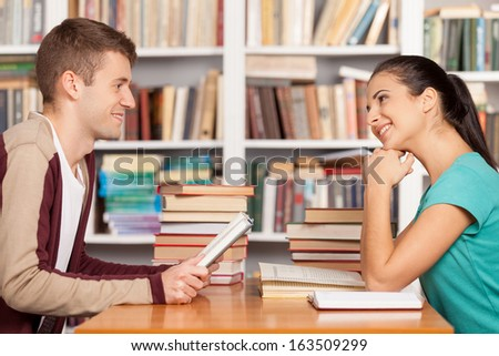 Friends in library. Cheerful young man and woman sitting at the library desk and smiling to each other