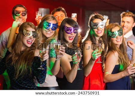 Friends in masquerade masks drinking champagne at the nightclub - stock photo