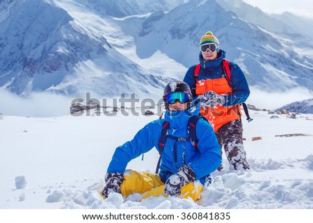 Friends in snowboard outfit playing snowballs in winter mountains - stock photo