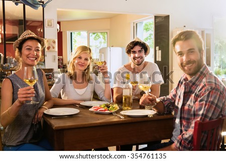 Friends in their 30s having a nice aperitif on a rustic wooden table in a lovely house. They are holding their high glasses of white wine. There are tomatoes mozzarella for starters. - stock photo