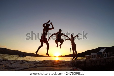 Friends jumping at sunset on the beach - stock photo