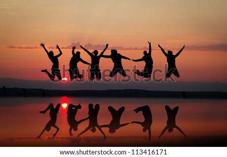 friends jumping in sunset - stock photo
