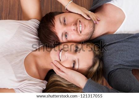 Friends lie alongside opposite heads on wooden floor. - stock photo