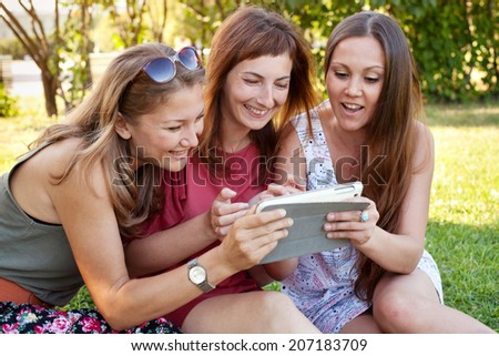 friends looking at the tablet and laughing - stock photo