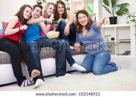 Friends looking something funny on TV and laughing, sitting in living room - stock photo