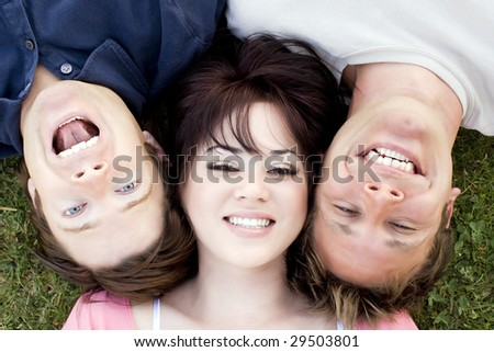 Friends lying in the grass together - stock photo