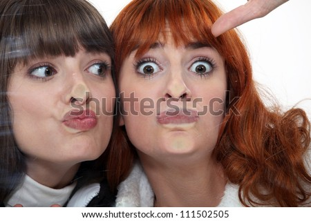Friends making a silly face against a windowpane - stock photo