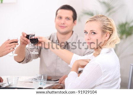 Friends making a toast at the dinner table - stock photo