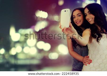 """Friends making selfie. Two beautiful young women making """"selfie"""". - stock photo"""