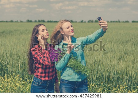Friends making selfie. Two beautiful young women making selfie and grimacing. In  field with flowers - stock photo