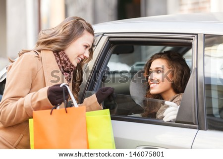 Friends meeting in town. Two female friends meet each other on the street while one of them sitting on the back seat of a car - stock photo