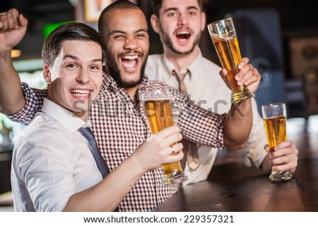 Friends meeting. Men shout and rejoice in meeting and drink beer. Three other men drinking beer and having fun together in the bar - stock photo