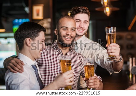 Friends met after a hard day. Three cheerful friend clink beer at the bar and drink a beer while the bartender is standing on the bar. Friends having fun together - stock photo