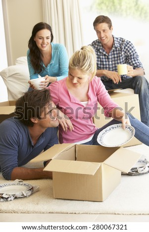 Friends Moving Into New Home Unpacking Boxes - stock photo