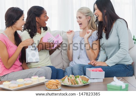 Friends offering gifts to woman during party at home on couch - stock photo