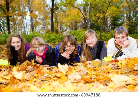 Friends on autumn leaves, laughing - stock photo