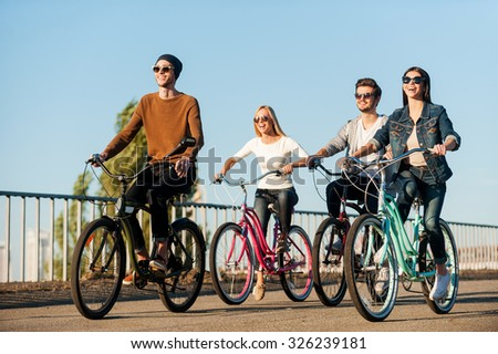 Friends on bicycles. Full length of four young people riding their bicycles and smiling