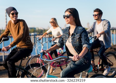 Friends on bicycles. Group of young people riding their bicycles and smiling - stock photo