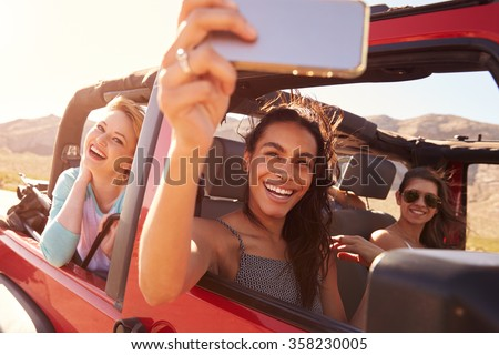 Friends On Road Trip In Convertible Car Taking Selfie - stock photo