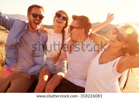 Friends On Road Trip Sitting On Hood Of Convertible Car - stock photo