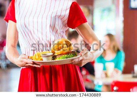 Friends or couple eating fast food and drinking milk shakes on bar in American fast food diner, the waitress wearing a short costume - stock photo