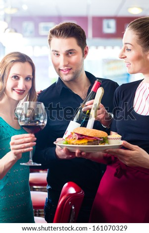 Friends or couple eating fast food in American fast food diner, the waitress serving the food, burgers, fries, and red wine - stock photo