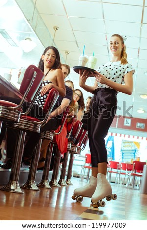Friends or couples eating fast food and drinking milk shakes on bar in American fast food diner, the waitress serving with roller-skates - stock photo