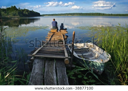 friends or father and son fishing on the lake - stock photo